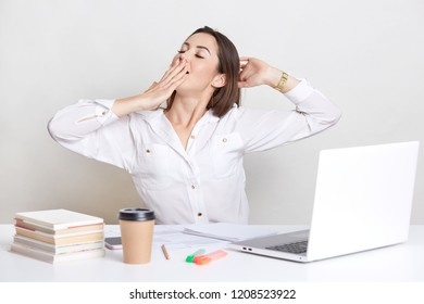 Sleepy European woman yawns and stretches, keeps hand on mouth, wears white shirt, uses laptop computer, books, isolated over white background. Businesswoman preprares project, poses indoor.