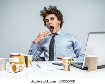 Sleepy exhausted young manager in yawn. Modern businessman at the workplace working with computer, depression and crisis concept