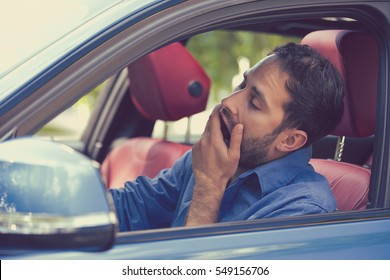 sleepy fatigued yawning exhausted young man driving his car in traffic after long hour drive. Transportation sleep deprivation accident concept