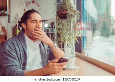 sleepy funny man, hand on mouth yawning looking at smart phone being bored by phone conversation, texting. Closeup portrait of a guy wearing casual wear sitting near window at table in coffee shop