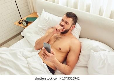 眠い紳士がベッドに横たわり、スマートフォンでメッセージをチェックしている