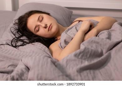 sleepy girl brunette in burgundy top under grey sheets in bed. morning routine. dream, sleeping. copy space