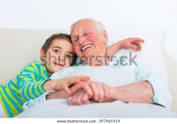 Sleepy grandmother preparing to sleep with her loving grandchild.