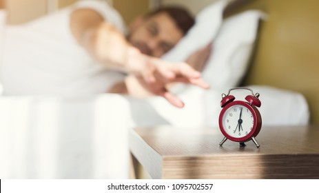 Sleepy guy waking up early after hearing alarm clock signal on monday morning, reaching button on the clock to turn it off, feeling tired and does not want to get up, copy space
