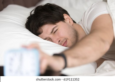 Sleepy guy waking up early after hearing alarm clock signal on monday morning, with eyes still closed reaching button on the clock to turn it off, feeling tired and does not want to get up