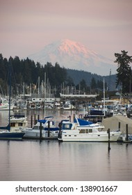 The sleepy harbor of the town of Gig Harbor with Mt Rainier catching the light from sunset in the background