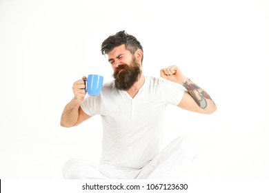 Sleepy hipster with beard holds mug in hand. Man with sleepy face stretching try to awake with cup of coffee. Morning coffee concept. Man needs to get up early in morning, white background.