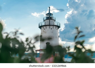 Sleepy Hollow Lighthouse on a beautiful summer's day, against a blue sky with white clouds and bokeh foliage in the foreground, medium shot, Sleepy Hollow, Upstate New York, NY