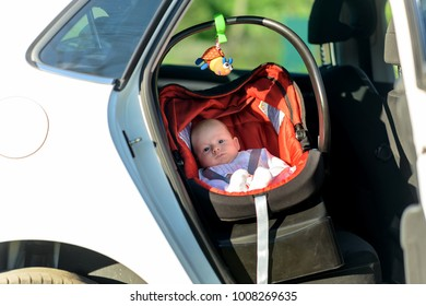 Sleepy little baby in a colorful red and black carrycot on the back seat in a car viewed through the open door
