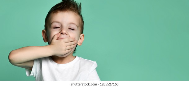 sleepy little boy yawning and looking at camera isolated on green