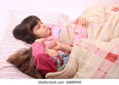 Sleepy little girls just waking up in bed, one still sleeps