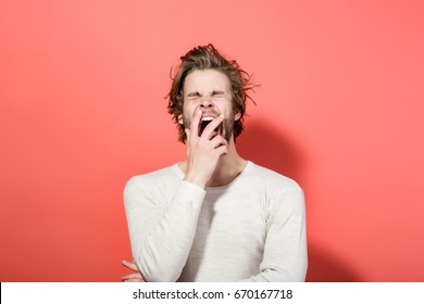 sleepy man with disheveled and uncombed long hair with beard on yawning face in white underwear on red background, morning and wake up, everyday life