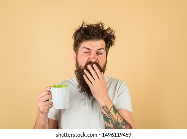 Sleepy man holds cup of coffee. Yawning man holds mug with hot drink.Man with cup of fresh coffee. Tired guy hold coffee mug. Morning refreshment. Man with sleepy face try to awake with cup of coffee.