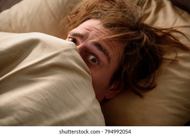 Sleepy man looking at camera with panic and lying in bed while covering his face with a blanket in bedroom. Close up