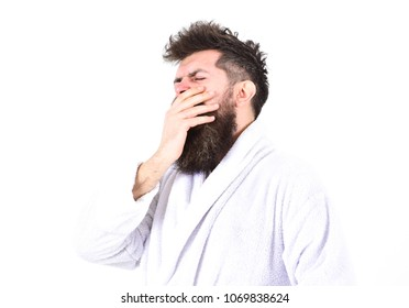 Sleepy morning concept. Guy drowsy with tousled hair. Macho in bathrobe on strict face looks sleepy. Man with beard and mustache yawning and covering mouth with palm, isolated on white background.