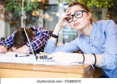 Sleepy overworked business people sitting and sleeping in meeting room