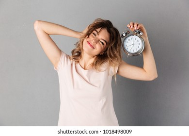 Sleepy smiling woman in t-shirt wake up while holding alarm clock and looking at the camera over grey background