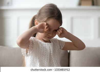 Sleepy stressed tired upset little child crying rubbing eyes feel abused hurt pain, sad lonely worried preschool kid girl in tears miss parents sitting on sofa alone, unhappy children emotion concept