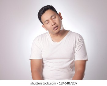 Sleepy tired funny young Asian man yawning, sleeping while sitting, half body portrait over grey background