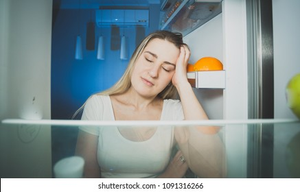 Sleepy tired woman leaning on refrigerator door a tnight
