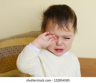 Sleepy toddler child crying in a bed after waking up or before going to sleep.