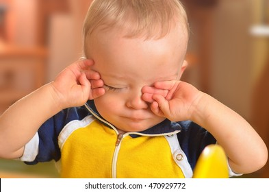 Sleepy toddler rubs his eyes. It is bedtime and child is sleepy. Child concept.