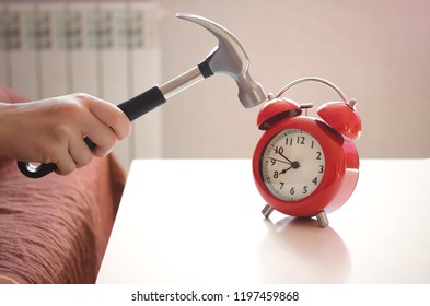 Sleepy woman in the bed is trying to smash a red alarm clock by hammer in her hand. Kill the alarm clock concept.