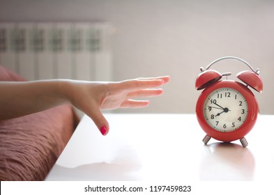 Sleepy woman in the bed is trying to turn off a red alarm clock on the table at morning time.