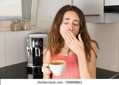 Sleepy woman in the morning drinking coffee