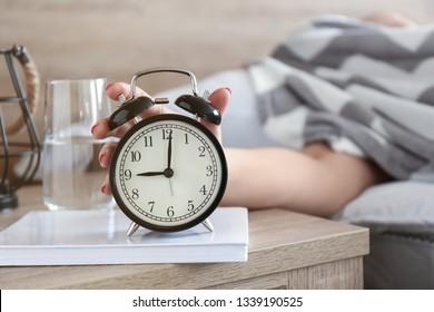 Sleepy woman turning off alarm clock in morning