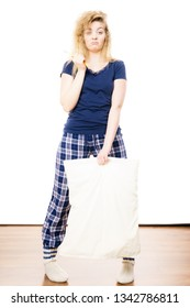 Sleepy woman wearing blue pajamas holding pillow, sleep outfit blue tshirt and checked trousers
