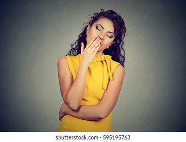 sleepy woman with wide open mouth yawning eyes closed looking bored isolated on gray wall background. Human face expression emotion