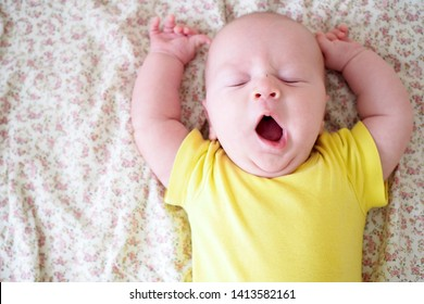 Sleepy yawning baby with hands up in parents bedroom