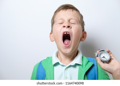 Sleepy and yawning schoolboy with blue backpack and with an alarm clock on a white background