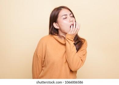 Sleepy young Asian woman yawn on beige background