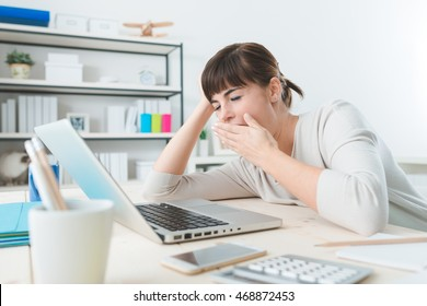 Sleepy young business woman sitting at office desk, working with a laptop and yawning