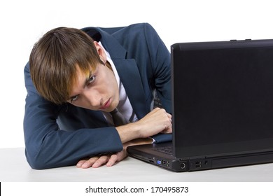 sleepy young caucasian businessman on desk with laptop