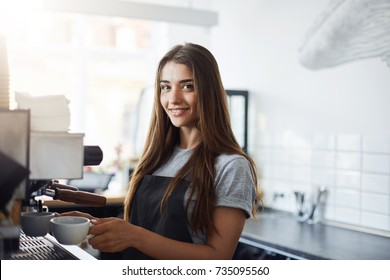 Sleepy young female starting her day on a new job as a barista. Looking happy and smiling at camera. Working in a cafe.