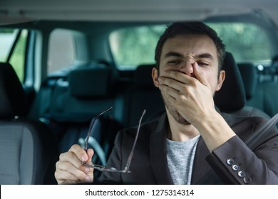 Sleepy young guy yawns while covering his mouth with his left hand. He is holding glasses at his right hand. Road safety concept.