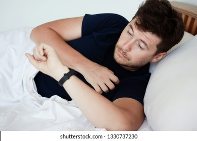 Sleepy young handsome caucasian man awake in early morning in his badroom and looking at alarm watches or fitness-tracker. Troubles with healthy sleep and tired after night sleep concept.