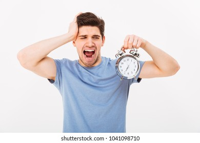 Sleepy young man 30s with brown hair holding alarm clock and yawning in morning isolated over white background