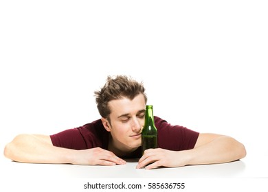 sleepy young man with a bottle of beer sitting at table, isolated on white
