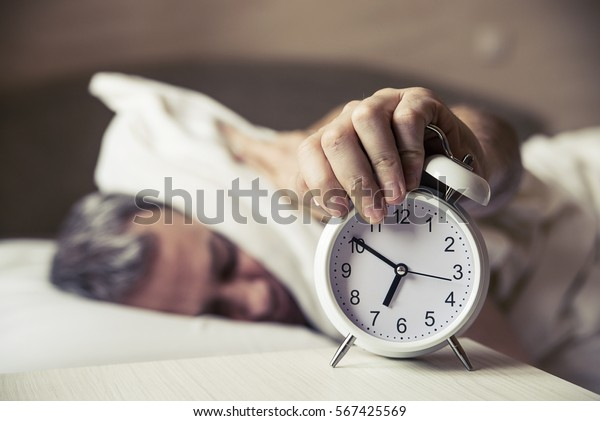 Sleepy young man covering ears with pillow as he looks at alarm clock in bed. sleeping man disturbed by alarm clock early morning. Frustrated man listening to his alarm clock while relaxing on his bed
