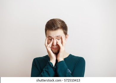 Sleepy young man rubbing eyes on a light background