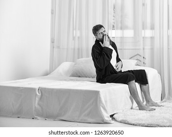Sleepy young man sitting and yawning in bed at home. Awakening concept. Macho with beard and mustache sluggish getting up and yawning in morning. Man in robe sits on bed, white curtains on background.