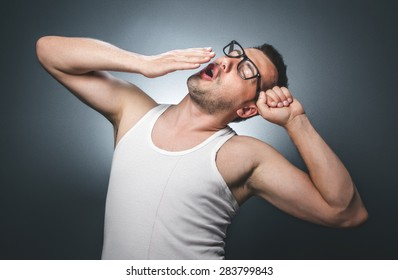 Sleepy young man wearing white undershirt. Funny guy yawn, comic facial exspression over gray dark background