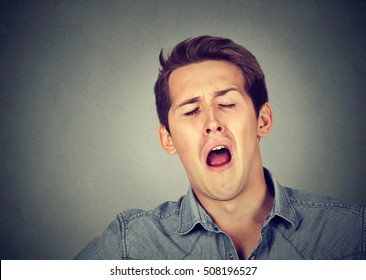 Sleepy young man yawning. Sleep deprivation, burnout, laziness concept
