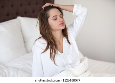 Sleepy young woman feeling drowsy or dizzy after waking up in bed, suffering from lack of sleep deprivation, insomnia, morning headache or migraine, having hangover after sleepless night concept