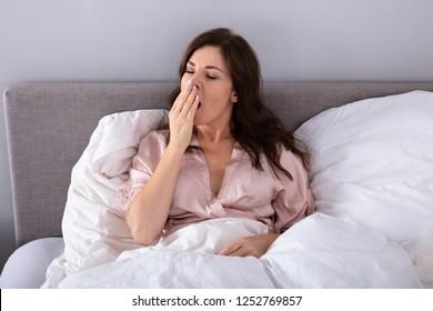 Sleepy Young Woman Lying On Bed In Bedroom