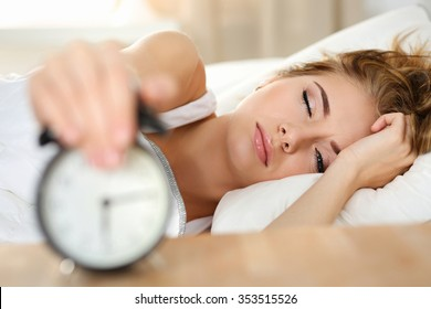 Sleepy young woman portrait with one opened eye trying kill alarm clock. Early wake up, not getting enough sleep, going work concept. Female stretching hand to ringing alarm willing turn it off.